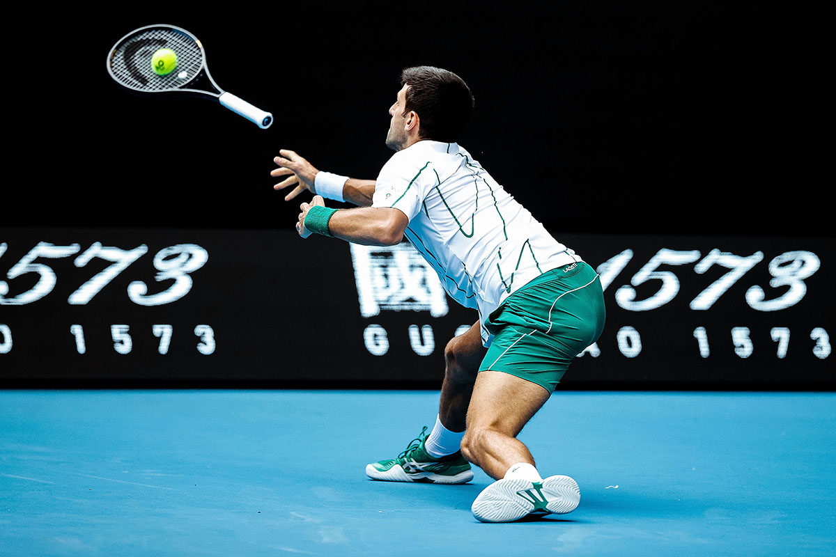 Serbia's Novak Djokovic throws his racquet to attempt to return the ball © Darrian Traynor/Getty Images