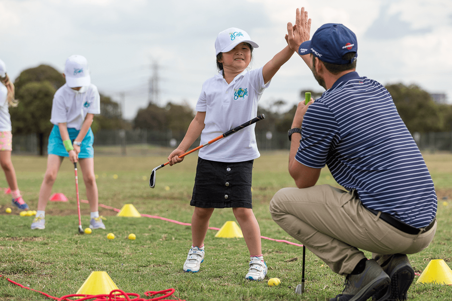 Young girl wearing white cap and golf shirt holds a golf club while high-fiving a golf coach.
