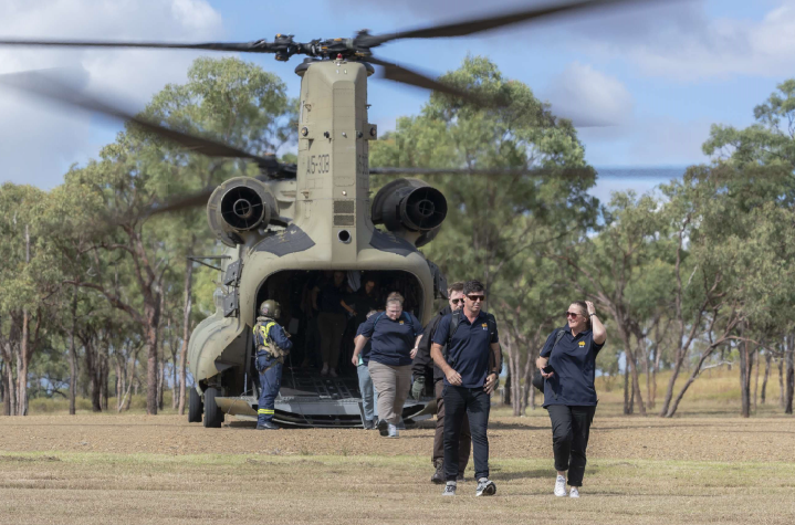 AIS representatives exit an Australian Army CH-47 Chinook en route from Townsville.