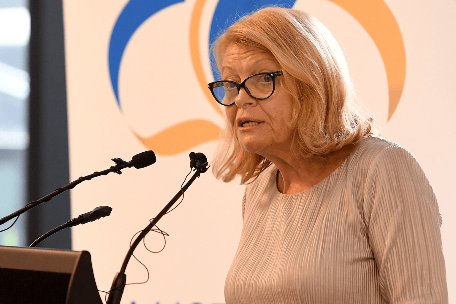 Lynne Anderson stands at a lectern speaking into microphones